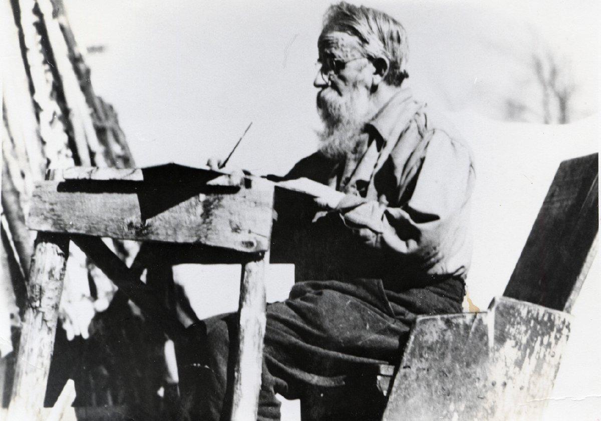 Noah John Rondeau writing at his outside desk, c. 1940 (P029046)