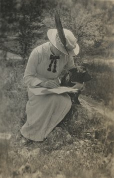 A woman writing with her pup. c. 1900-1914. (P025434)